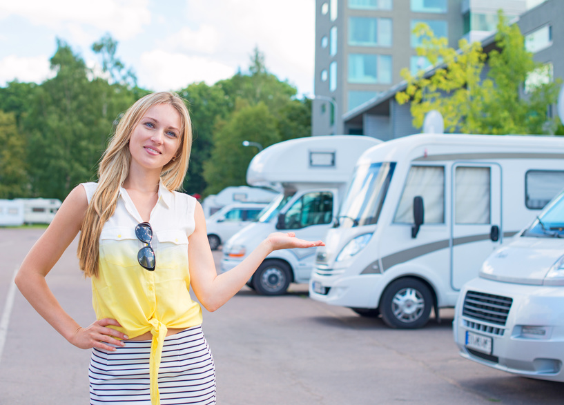Beautiful young woman offers campervans at shop. - P